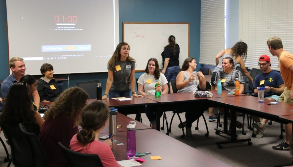 Chelsea Bonnain (standing, center) leads her fellow CMS graduate students in a panel discussion on Communicating Your Science. The group practiced 1-minute, 30-second, and 15-second elevator pitches of their research to the seated REU students.