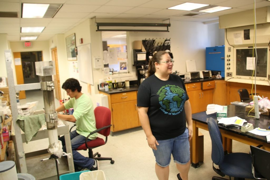 Mya Breitbart, microbiological oceanographer, directs the attention of the REU group to Eckerd College student Duke Thornburgh (shown seated), who is preparing sections of a sediment core for analysis