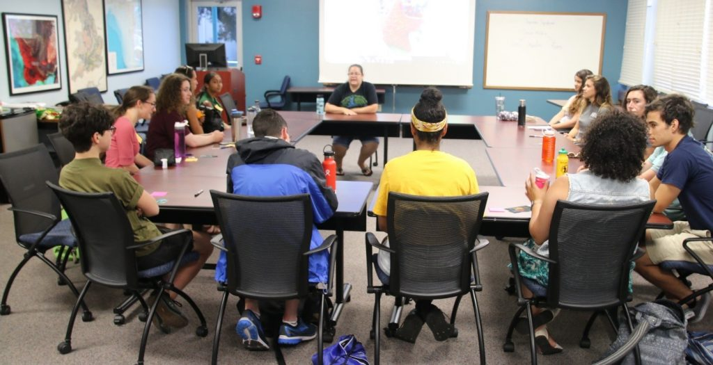 Mya Breitbart (seated, top center) conducts a round-table style seminar on the art of using social media as an outlet for scientific research