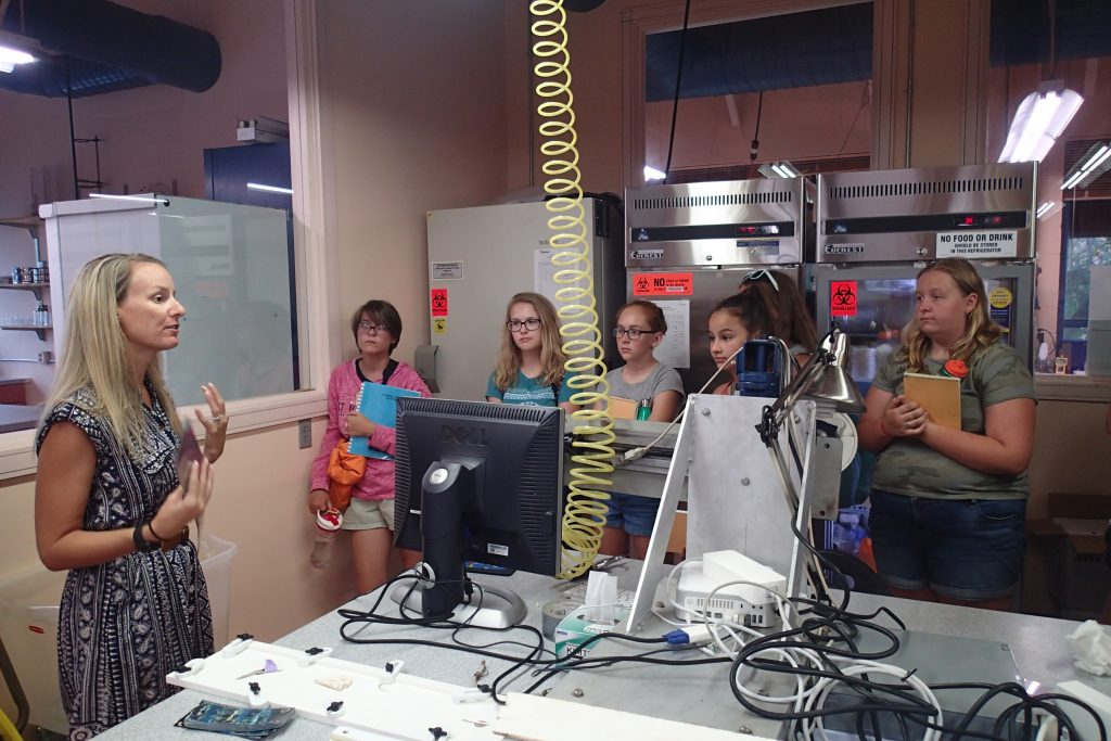 Participants from the Oceanography Camp for Girls listen as Jennifer Flannery (USFCMS Grad '08) from the USGS explains her work. Photo credit: OCG Staff
