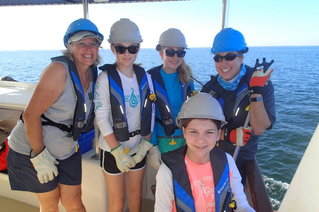 Camp director, Dr. Teresa Greely, posing with campers and an R/V ANGARI staff member before conducting a plankton net tow. Photo credit: OCG Staff