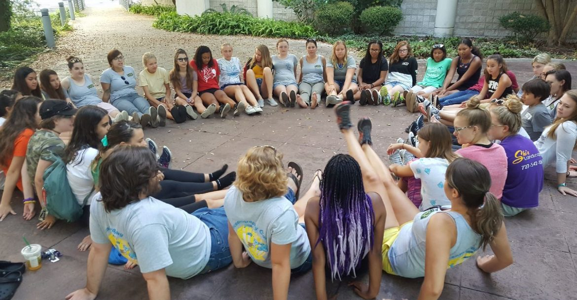 OCG campers and mentors sit in a circle to discuss science