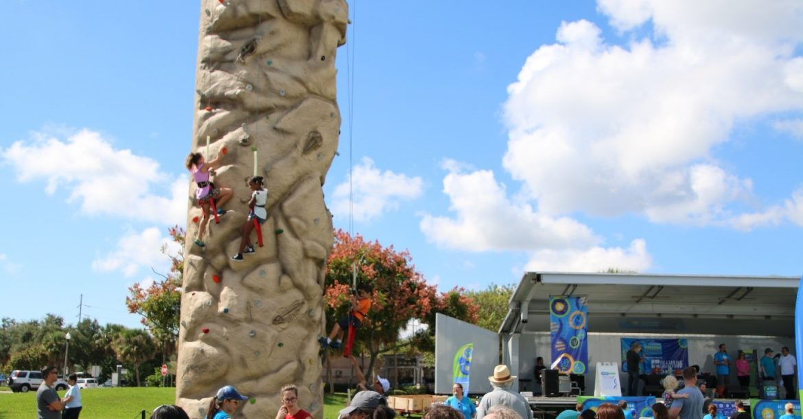 Young climbers take on the rock wall in the foreground of the Poynter Park Stage at the 2018 St. Petersburg Science Festival