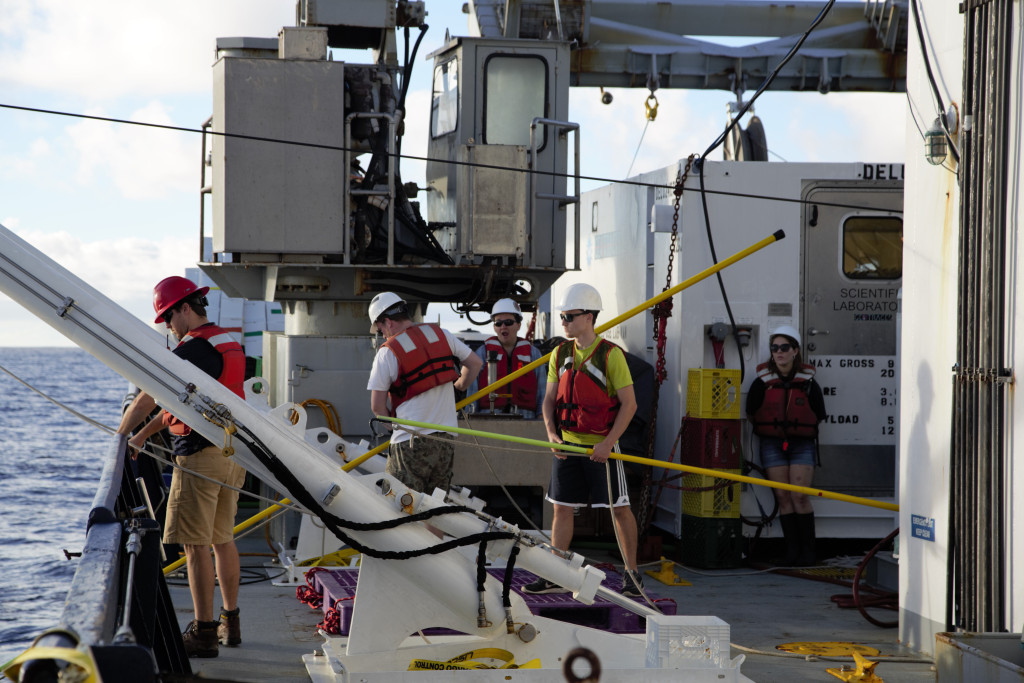 Laramie Jensen, Brent Summers and other members of the GP15 team prepare to retrieve the trace metal clean CTD rosette. Telescoping poles are used to attach tag lines. Photo Credit: Alex Fox