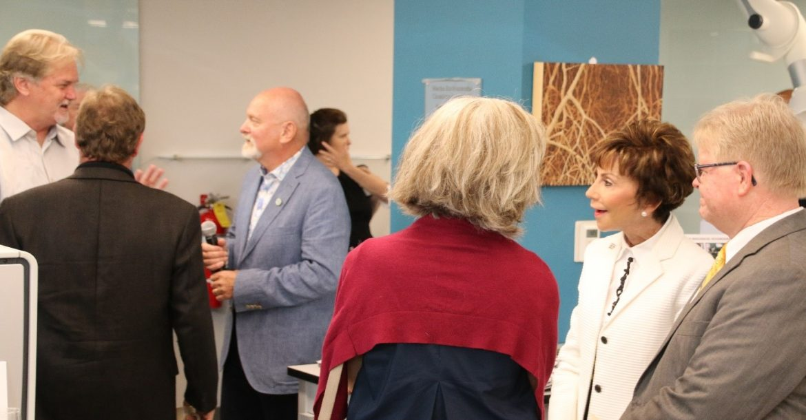 USF President Judy Genshaft (white coat, foreground) and Dr. Steve Murawski (blue coat, background) converse with other guests after giving speeches at the grand opening of the Marine Environmental Chemistry Laboratory at USFCMS.