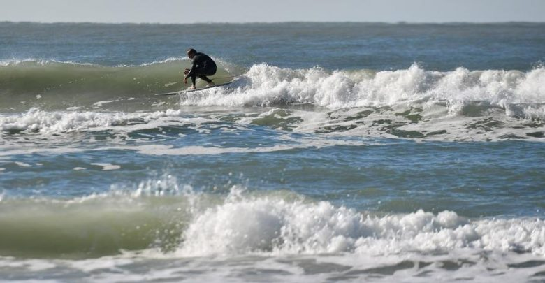 A surfer on Siesta Beach takes advantage of swells created by a storm front that brought windy weather over the weekend. Morning temperatures dipped into the low 40s across the area. Photo Credit: Herald-Tribune staff photo / Mike Lang