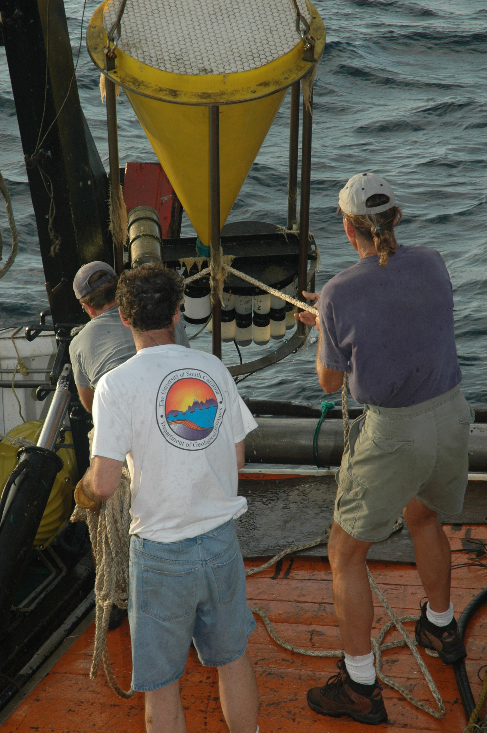 "A CARIACO team recovers a sediment trap (Eric Tappa in white shirt, University of South Carolina; Rick Cole in blue shirt and Jason Law from USF in grey shirt). Analyses revealed that more than 5% of carbon particulates from the surface reach 275 m depth, and nearly 2% reach 1,400 m. This flux represents a ""sink"" for carbon and helps explain the record of ancient climate stored at the bottom of the Cariaco Basin."