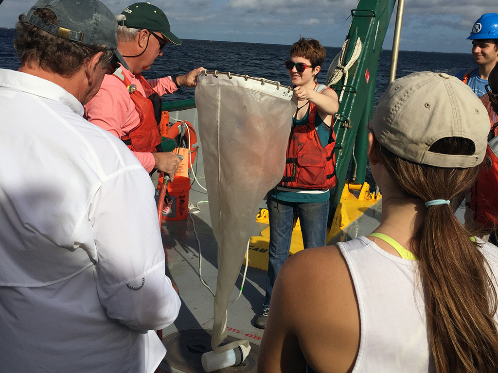 A student, Alyssa Anderson, and Dr. Ernst Peebles rinse the plankton net to collect plankton.