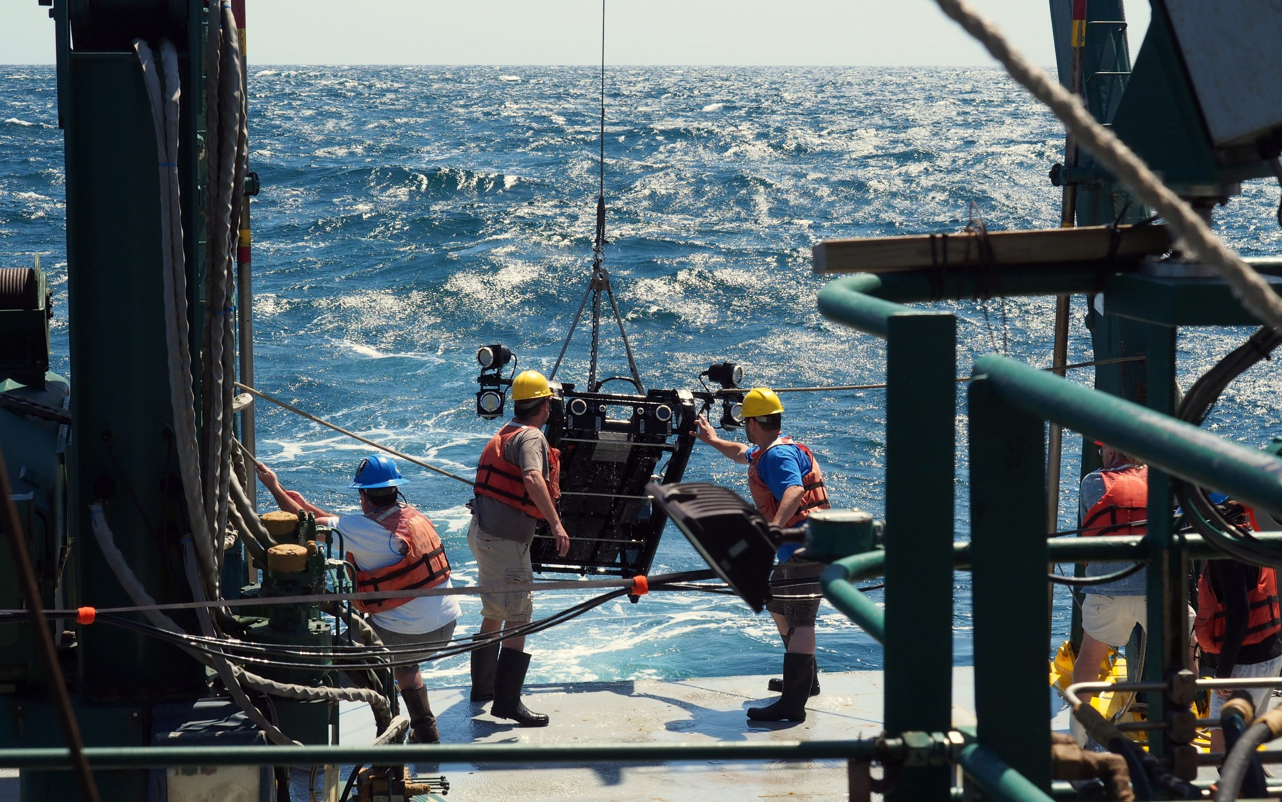 Recovery of the video tow platform C-BASS in April 2016 following a near bottom tow to collect bottom habitat and fish density distributions in the eastern Gulf of Mexico (In photo left to right Edmund Hughes, Chad Lembke, Alex Silverman, Steve Butcher, vessel R/V Weatherbird, photo credit Matt Hommeyer)
